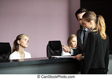 Business people at front desk - Business people filling...