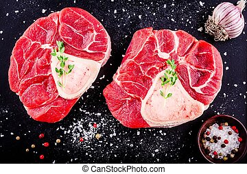 two raw fresh veal shank meat for ossobuco on dark...
