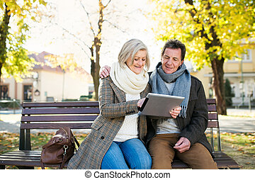 Senior couple with tablet sitting on bench. Autumn park. -...