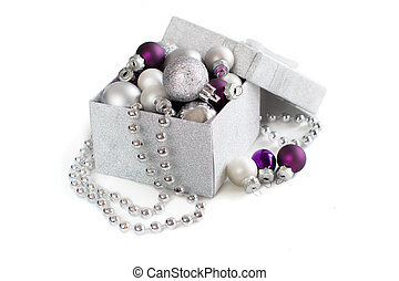 Silver and purple Christmas ornaments in gift box on white...