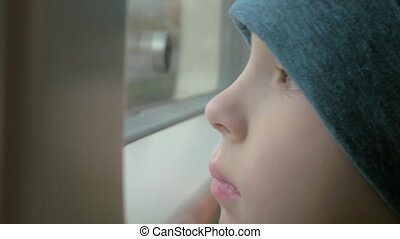 In train rides a little boy in a cap who looks out the...