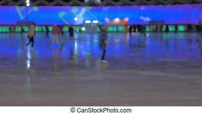 People on skating-rink at night - Defocused shot of many...