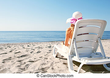 Pregnant woman in a lounge chair on the beach