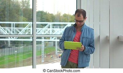 Programmer in black rim glasses using his tablet computer at...