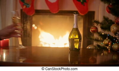 Closeup of hands of couple in love taking glasses of champagne and clinking at fireplace decorated for Christmas