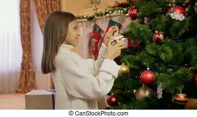 Portrait of cute girl in white sweater decorating Christmas tree
