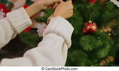 Closeup of girl decorating Christmas tree. Camera zooms in from hands to bauble