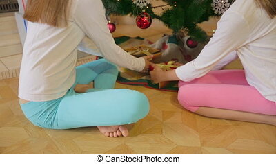 Two girls in pajamas sitting under Christmas tree and open Christmas presents