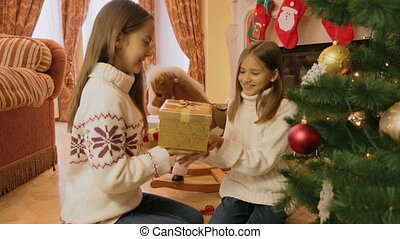Two cheerful girls giving Christmas presents to each other and opening them