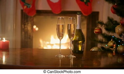 Couple in love celebrating New Year and clinking with glasses of champagne at fireplace. Closeup of hands with glasses