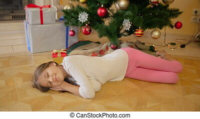 Mother giving Christmas gift to her girl that fell asleep on...