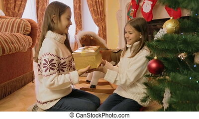 Portrait of two cheerful girl receiving Christmas gifts and hugging each other