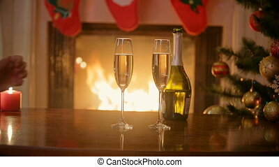 Closeup of man and woman sitting at fireplace and drinking champagne at Christmas eve