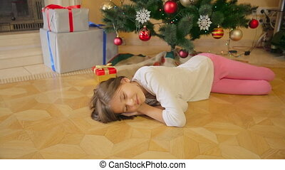 10 years old girl sleeping under Christmas tree at morning. Mother leaving present on floor.