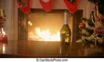 Hands of couple in love clinking glasses with champagne at Christmas eve. Man and woman sitting at burning fireplace at decorated living room.