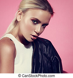 Sexy makeup blonde woman looking with black jacket on the shoulder on pink background. Closeup glamour portrait