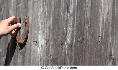 Country man hand hang old rusty horseshoes on old wooden door - symbol of luck. 4K