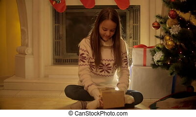 Cute teenage girl sitting at fireplace and opening Christmas...