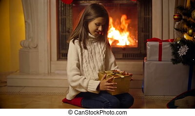 Cute girl in sweater opening magical Christmas gift box. Light and sparkles flying out of the box