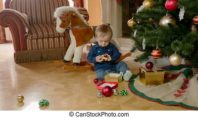 Adorable 1 year old baby boy playing under Christmas tree at...