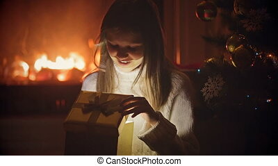 Closeup portrait of excited girl opening Christmas box and light shining from it