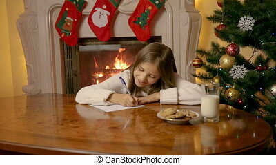 Beautiful 10 year old girl writing letter to Santa Claus...