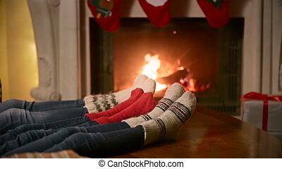 Family with child in knitted woolen socks warming at burning...