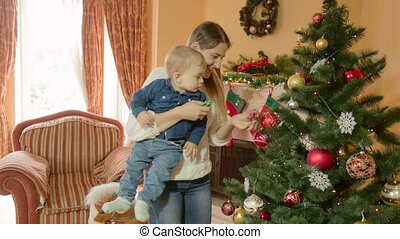 Happy young mother holding baby boy on hands and showing him Christmas tree. Concept of first Christmas in life