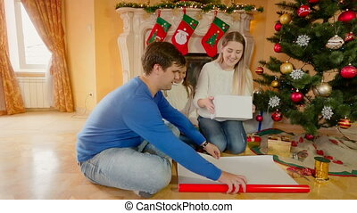 Young happy family sitting at living room and wrapping...