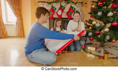 Happy family with girl wrapping Christmas gifts in red wrapping paper