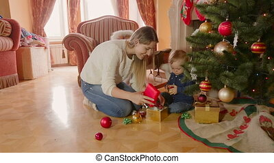 Young beautiful mother and 1 year old baby son playing under...