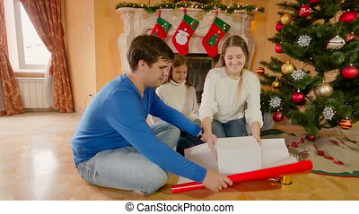 Happy family sitting on floor and wrapping Christmas...