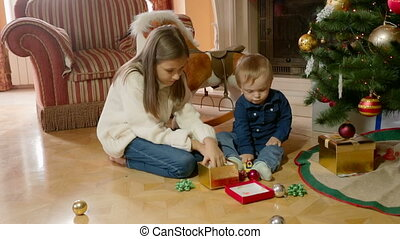 Cute girl playing with her little brother on floor under Christmas tree