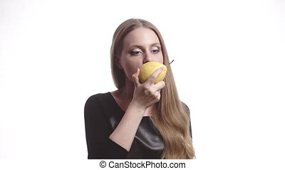 Beautiful young woman with red lips eating pear