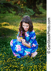 beautiful woman picking yellow flowers in a meadow