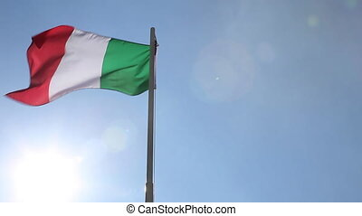 National flag of Italy on a flagpole in front of blue sky