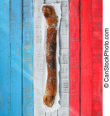 Baguette over a table with the colors of France flag.