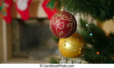 Closeup of beautiful red bauble hanging and spinning on Christmas tree next to decorated fireplace