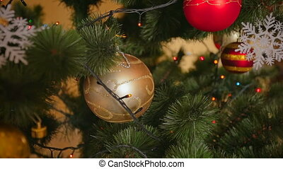 Closeup of beautiful golden bauble on Christmas tree with...