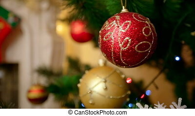 Closeup of golden and red baubles hanging on Christmas tree...