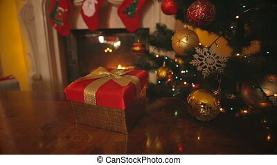 Dolly shot of red Christmas gift box with golden bow on...