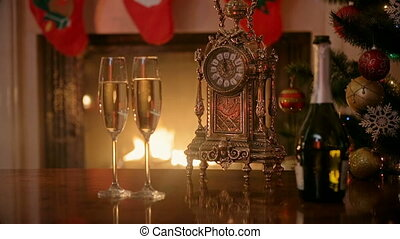 Two glasses of champagne and retro clock in front of burning fireplace at house. Concept of celebrating Christmas