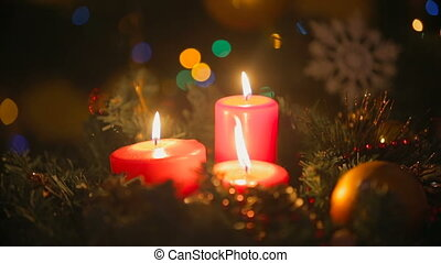 Closeup of Christmas wreath with three burning red candles....