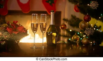 Christmas table with two glasses of champagne lit by burning...
