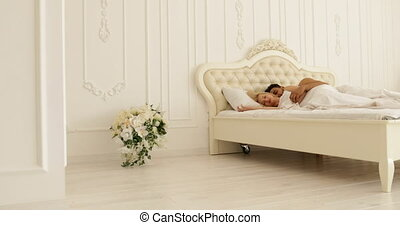 Couple sleep lying on bed man hug woman home white modern...
