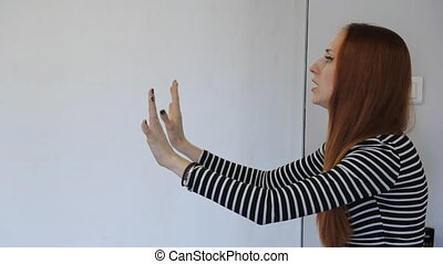 Ginger woman in striped blouse gives commands to other...