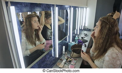 Up view of young female making up in model school....