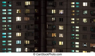 Time lapse shot of buildings and lighted windows at night -...