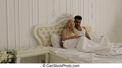 Couple lying bed using tablet computer, mix race man woman...