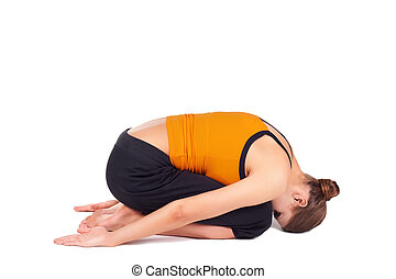 Woman Practicing Child Pose Yoga Asana - Fit woman doing...
